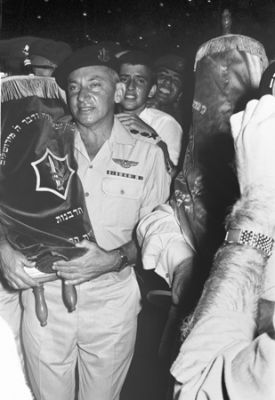 Chief of Staff Lt. Gen. Haim Bar-Lev holds a Torah during Simhat Torah celebration at Tzrifin base, early 1970s.