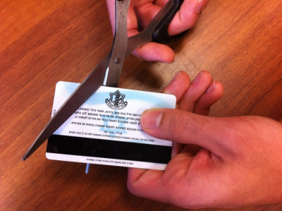 A soldier cutting his identification card at the end of his military service