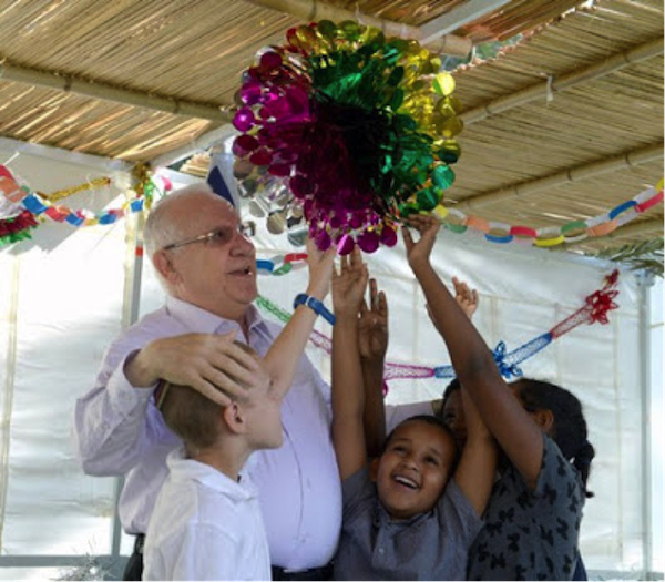 President Rivlin prepares his sukkah with the help of some local kids.  Photo: MFA.gov.il