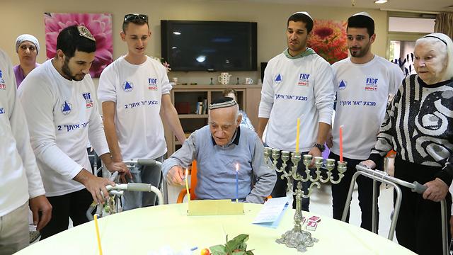 IDF soldiers celebrate Hanukkah with Holocaust survivors